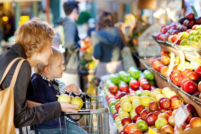 Moeder en kind kopen fruit in de supermarkt.