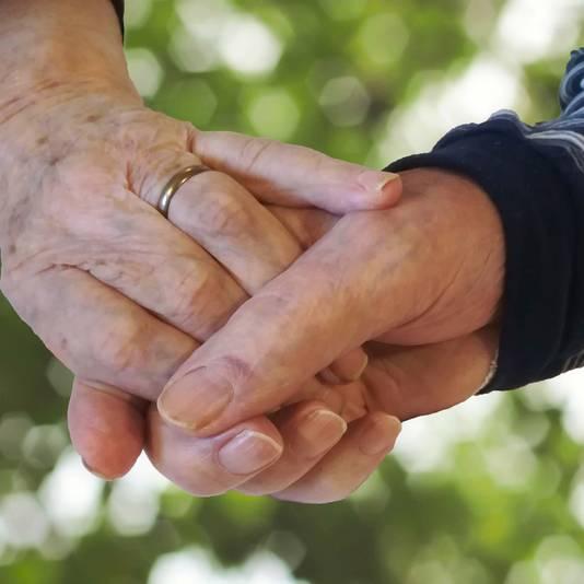 De verstrengelde handen van Harrie en Riek van de Wetering, zoals ze elkaar tot op het laatst vasthielden. Deze foto is in bed genomen, de familie heeft de achtergrond aangepast voor de overlijdensannonce.