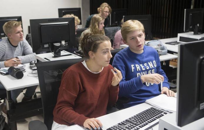 Studenten werken aan hun opdrachten tijdens het avondcollege.