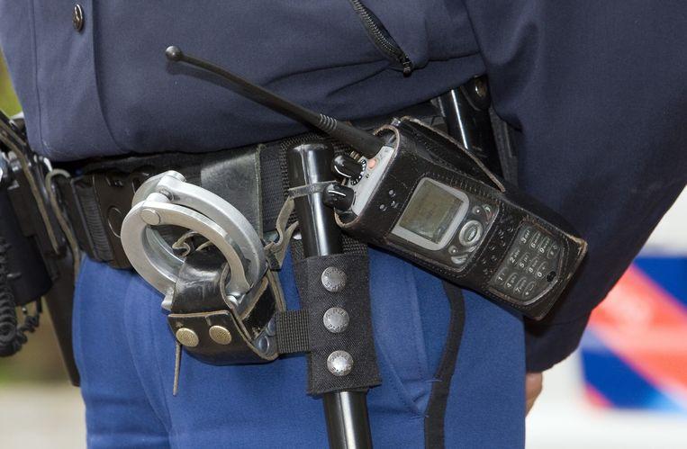 Een agent met een (in dit geval nog niet uitschuifbare) wapenstok aan zijn riem. Beeld ANP