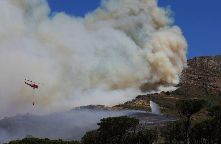 Een helikopter lost bluswater boven het gedenkteken voor de Zuid-Afrikaanse politicus Cecil John Rhodes op de Tafelberg. Beeld AP