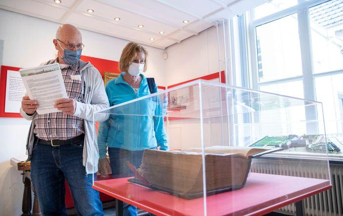Chris en Nelly van Haarlem bekijken de bijbel van Torck in museum De Casteelse Poort.