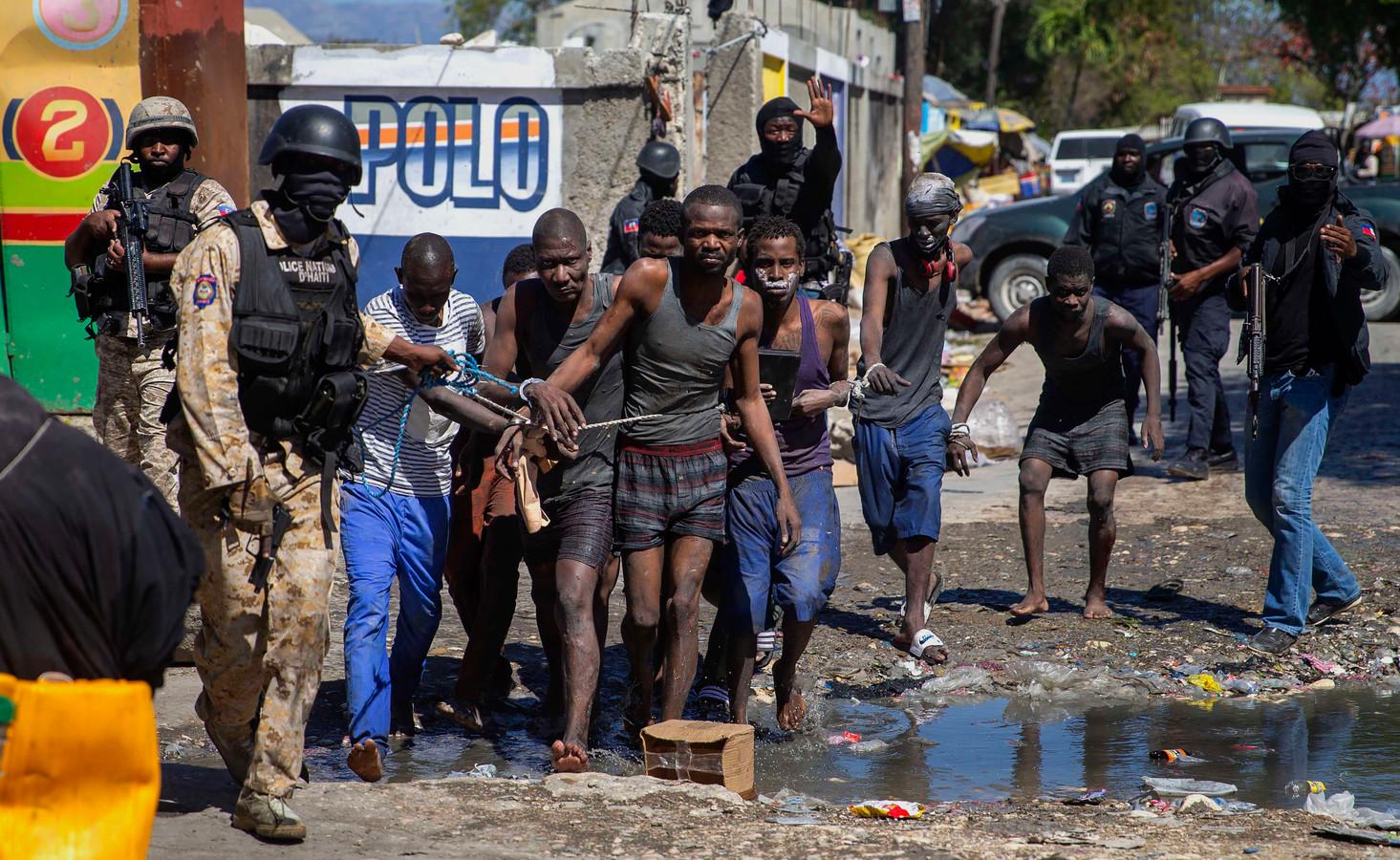 Ontsnapte en weer opgepakte gevangenen worden door de politie teruggebracht naar de gevangenis Croix-des-Bouquets in de Haïtiaanse hoofdstad Port-au-Prince.