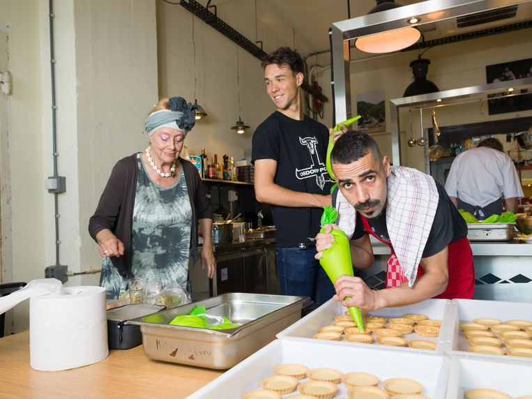 Abidin spuit citroencustard in deegvormpjes in de keuken. Links: buurtbewoner Chanel Vredevoogd. Beeld Ivo van der Bent