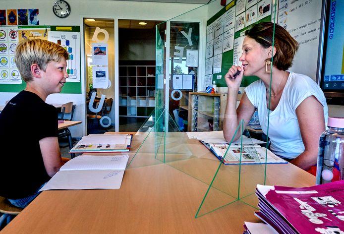 Leerkracht Josje Collé geeft op De Klinker in Oud-Beijerland soms les achter plexiglas.