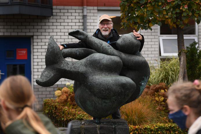 Ger Kroes bij het beeld De Zeemeermin op het schoolplein van College De Heemlanden.