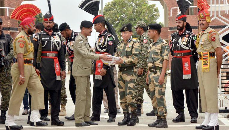 Onafhankelijkheidsviering aan de grens: de Pakistaanse commandant trakteert maandag zijn Indiase collega op snoepgoed. Beeld getty