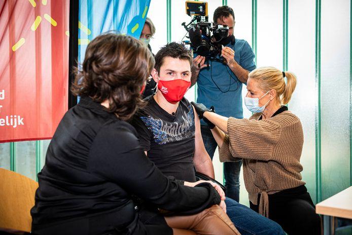Chris van der Werf (rood mondkapje) is cliënt van Ipse de Bruggen en wordt vandaag  als een van de eersten met het corona-vaccin gevaccineerd.