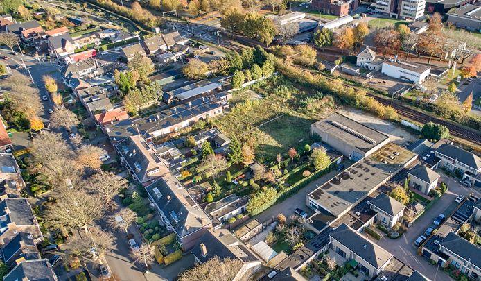 Het gebiedje tussen het spoor en de Kromstraat waar de 28 woningen moeten komen. Voormalig zalencentrum Tivoli en een transportbedrijf (de platte daken op de foto) worden gesloopt.