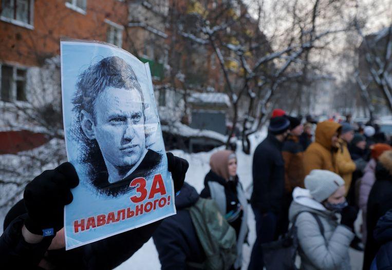 Een demonstrant draagt een protestbord met de tekst 'Voor Navalni!' bij het politiebureau waar de oppositieleider wordt vastgehouden.  Beeld Reuters