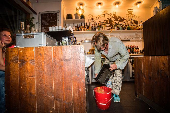 Kunstenaar Marcel Smink schudt koffiedrab in zijn emmer bij café Sugar Hill in Arnhem voor zijn kunstwerk Het Koffijhuis in Waalwijk.