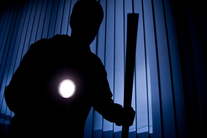 Burglar breaking in a residential house with lamp in hand