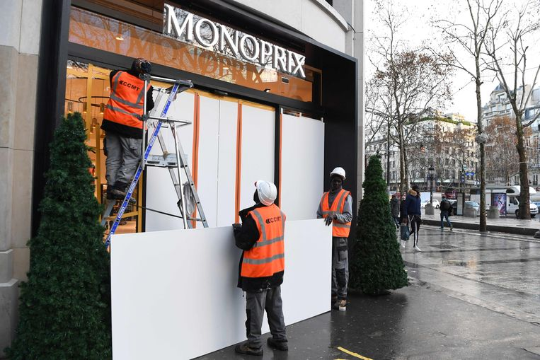 Arbeiders barricaderen winkeletalages op de Champs-Élysées. Beeld AFP