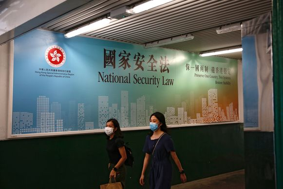 Vrouwen lopen langs een door de regering gesponsorde 'reclame' voor de nieuwe Chinese wet voor nationale veiligheid, die het land ook wil opleggen aan Hongkong.