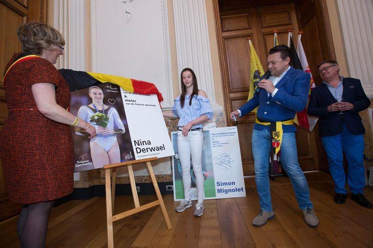 Burgemeester Veerle Heeren en schepen van Sport onthullen het bord voor Europees kampioene Nina Derwael. Ze wordt meter van de Truiense sportclubs.