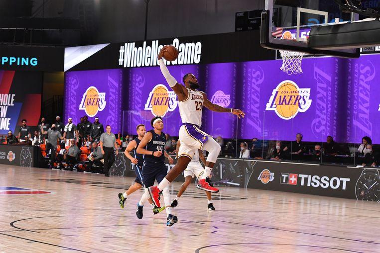 LeBron James, sterspeler van de Los Angeles Lakers, dunkt tijdens een oefenmatch tegen de Dallas Mavericks in Orlando. Beeld NBAE via Getty Images