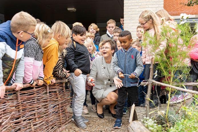 Burgemeester Ger van de Velde opent de tuin met hulp van leerlingen Giovanni (zwarte jas) en, Nefthalem (blauwe jas).