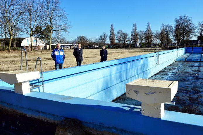 Aan het oude bassin van het buitenbad staan projectleiders Cees Aanraad en Tony Oomes met daarnaast wethouder Martien de Bruijn.