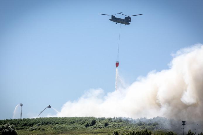 Een Defensie-helikopter probeert de grote brand in Hengelo te blussen.
