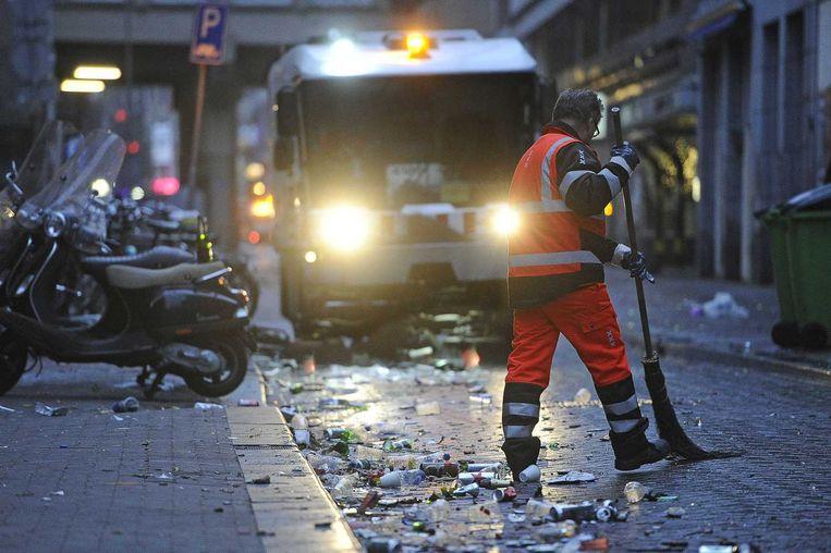 Een medewerker van de stadsreiniging veegt de restanten van het vuurwerk en ander afval bij elkaar. Beeld anp