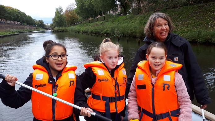Drie van de Oberon-leerlingen op de plastic boot met schipper Majel.