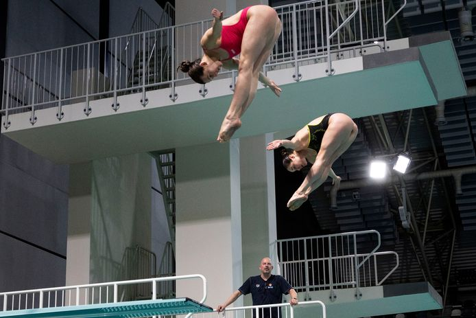 Edwin Jongejans geeft aanwijzingen aan Inge Jansen en Celine van Duijn op de 3-meterplank.