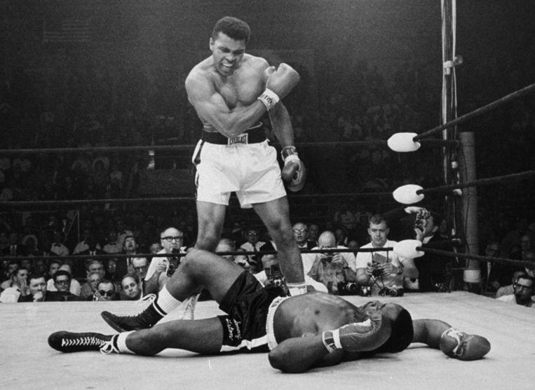 Muhammad Ali staat langs zijn overwonnen tegenstander Sonny Liston op 25 mei 1965. Beeld ap