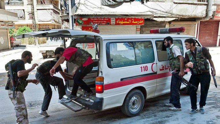 De Syrische rebellen leggen een gewonde strijder in een ambulance, in Aleppo. Beeld AFP