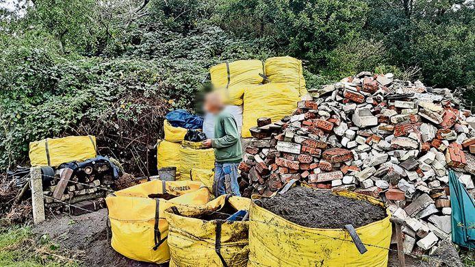 In een hoek van een vroegere vuilnisbelt bij Enschede, uit het zicht van iedereen, is een man bijna dagelijks bezig te graven en puin en ander afval te sorteren in 'big bags'.