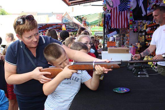 Een mama helpt zoonlief aan het schietkraam.