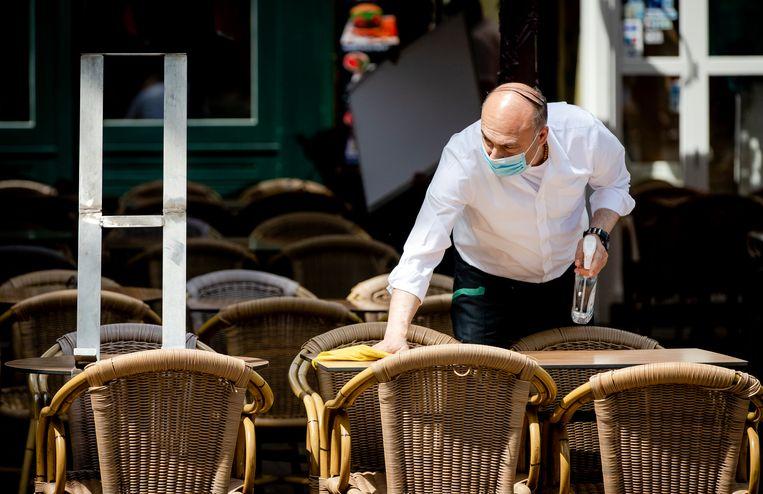Een medewerker desinfecteert een tafel op een terras aan het Rembrandtplein. Beeld ANP