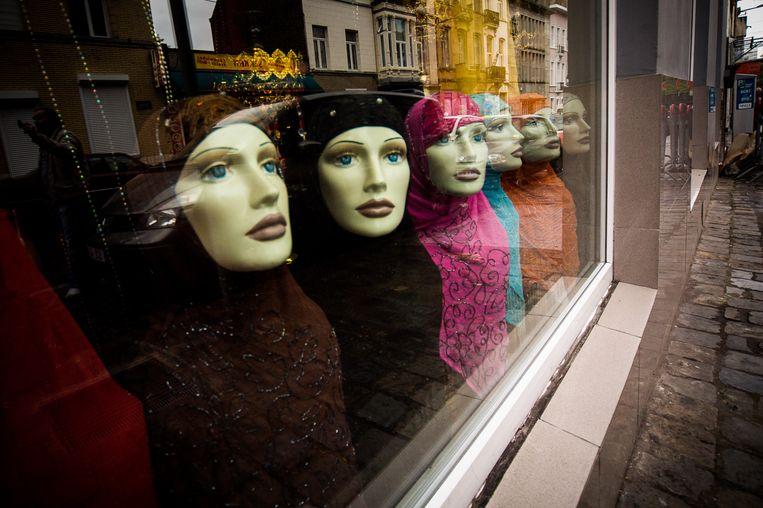 Kleurrijke 'hidjabs' of hoofddoeken in de etalage van een Brusselse speciaalzaak. Beeld BELGA