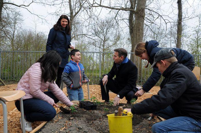 Het terrein achter de school is een moestuin geworden. De eerste plantjes gingen vandaag in de grond. Van links naar rechts:  Yasmine, Janneke Donkers (staand), Jaimy, gedeputeerde Jo-Annes de Bat, Yfke en David.