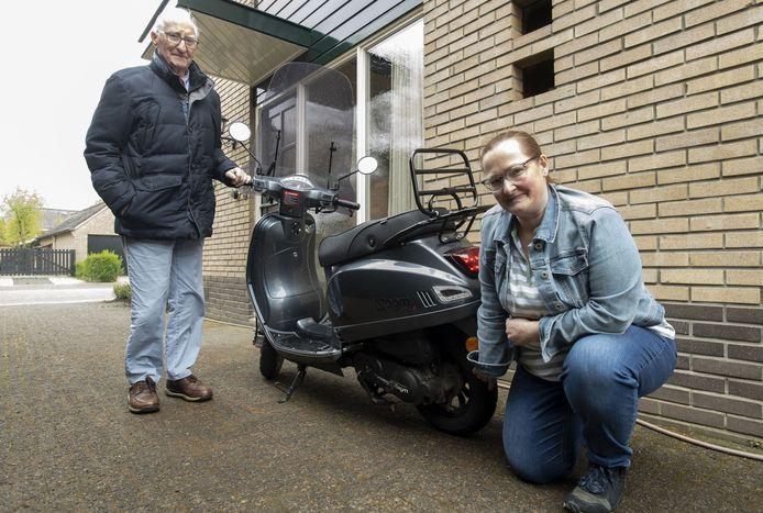 Carine Stegeman en haar vader bij  de scooter,  waarmee nu al vier lekke banden zijn 'gescoord'. De ijzeren pinnen van veegmachines zijn vermoedelijk de oorzaak.