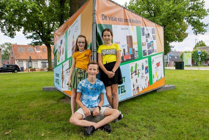 Kinderen van de basisschool in Gastel hebben meegedacht in het kader van de dorpsvisie. Hun wensen zijn te zien op drie grote doeken op het Cornelisplein. Op de foto staan Silke, Roos en Sven.