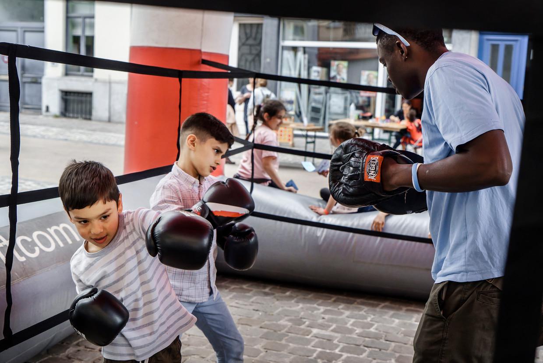 Kinderen krijgen boksinitiatie tijdens de buitenspeeldag in Elsene. Beeld Eric de Mildt