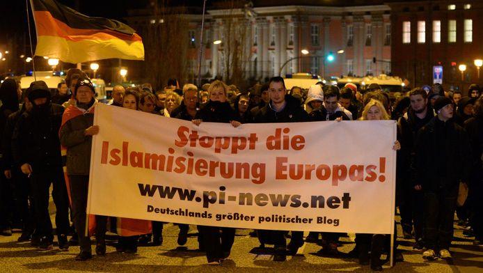 Demonstraten van Podiga, een zijtak van Pegida, protesteren voor het parlementsgebouw in de Duitse stad Potsdam.