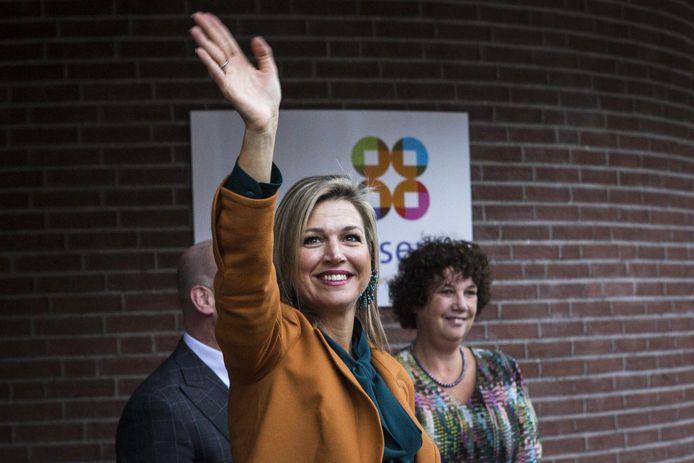 Koningin Máxima zwaait naar de menigte voor buurthuis De Mussen. Rechts Mussen-directeur Nicoline Grötzebauch.