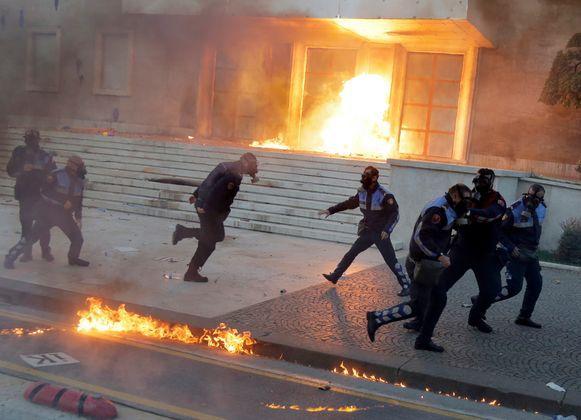 Politiemannen proberen de vlammen van een benzinebom te ontwijken in de Albanese hoofdstad Tirana.