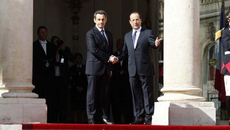 Uittredend president Nicolas Sarkozy schudt handjes met de nieuwe president François Hollande op de trappen van het Elysée, waar Hollande voortaan zal wonen. Beeld REUTERS