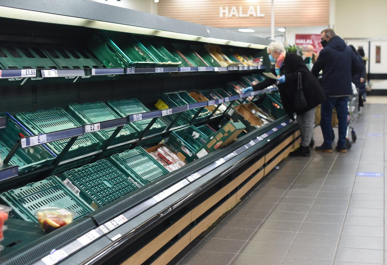 Lege rekken in de afdeling groenten en fruit in een filiaal van supermarktketen Tesco in Londen. Beeld Photo News