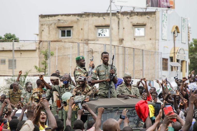 Gewapende militairen worden toegejuichd in de straten van Bamako, Mali, na hun arrestatie van president Keïta en  premier Boubou Cissé. Beeld AFP