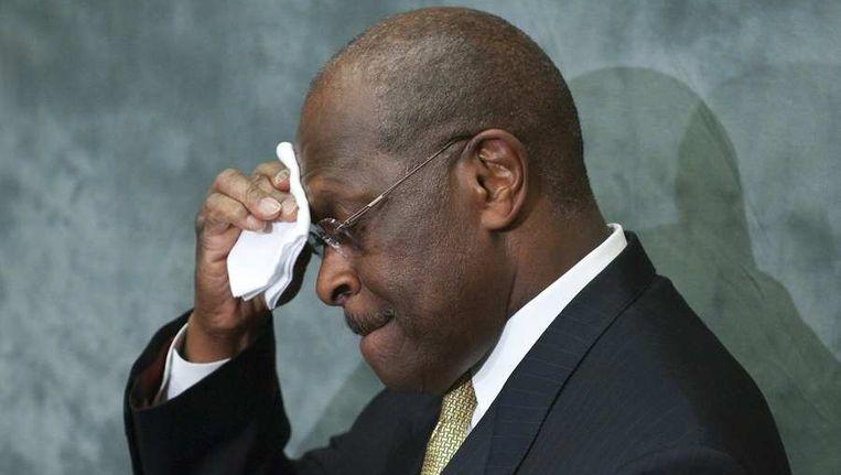 Herman Cain veegt zijn voorhoofd af vlak voor een persconferentie. Beeld reuters