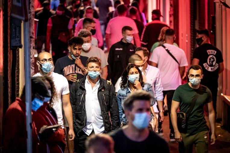 Toeristen met mondkapjes op de Wallen in Amsterdam. Beeld Hollandse Hoogte /  ANP