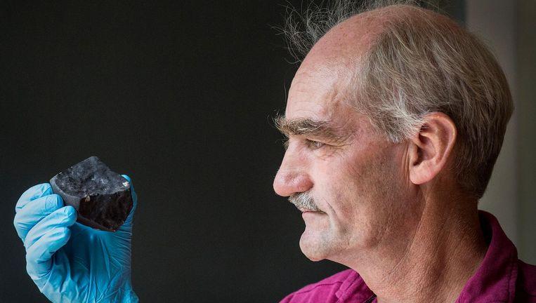 Leo Kriegsman van Naturalis bestudeert de meteoriet die in januari een dakpan in Broek in Waterland verpulverde. Beeld Arie Kievit / de Volkskrant