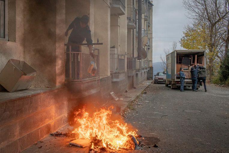 Een man verbrandt de spullen die hij niet kan meenemen, terwijl anderen een verhuiswagen volladen in Lachin.  Beeld Anush Babajanyan