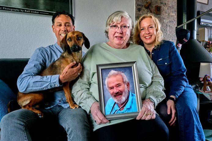 """Reina Bosman houdt de foto van haar man vast en is omringt door haar dochter Bianca de Graaff-Bosman, schoonzoon Lothar de Graaff en hun hondje Tara. ,,Hij was gek op dat beest. Een van zijn laatste woorden was haar naam."""""""