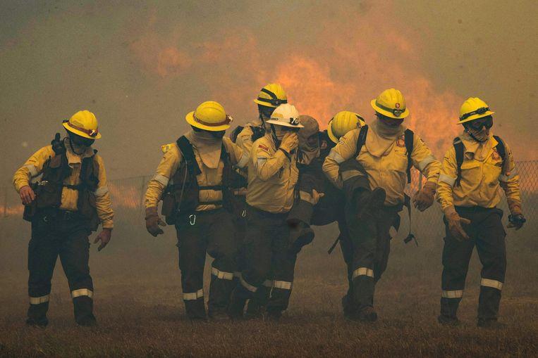 Brandweerlieden dragen een onwel geworden collega. Beeld AFP