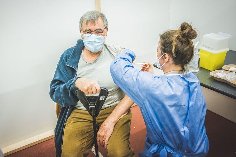 Een man wordt ingeënt met een coronavaccin in het vaccinatiecentrum in Deinze. Beeld Wannes Nimmegeers
