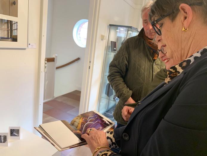 Fotografe Cootje Versteeg-Mandemakers bladert samen met een bezoeker door een fotoserie heen